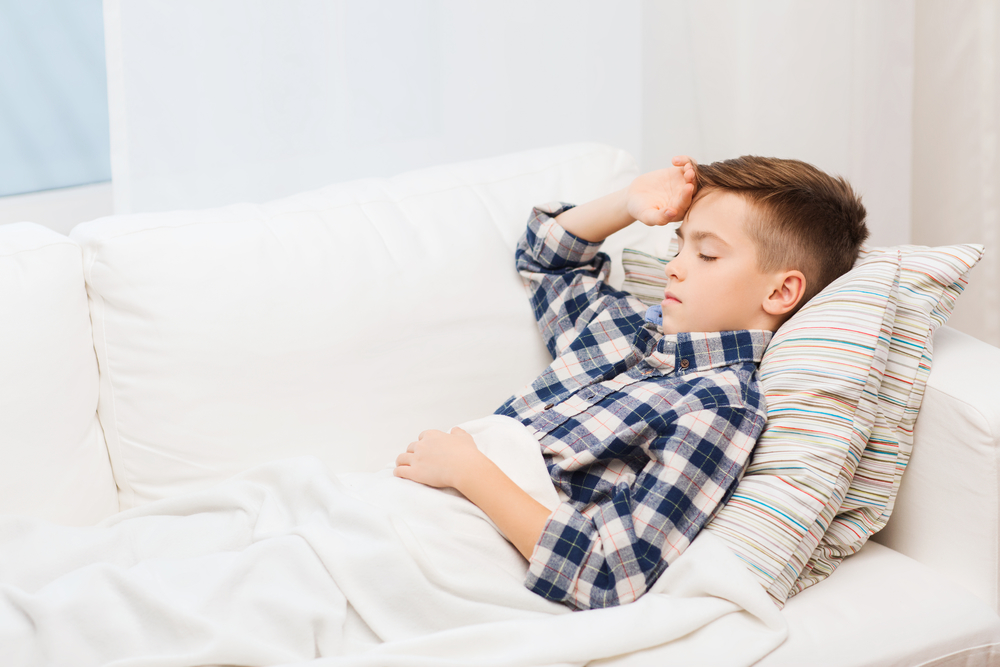 childhood, healthcare, people and medicine concept - ill boy with flu lying in bed at home and suffering from headache